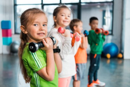 Photo pour Concentration sélective des enfants multiethniques alignés, tenant des haltères et souriant dans le centre sportif - image libre de droit