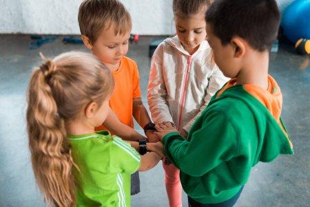 Photo pour Vue en angle élevé d'enfants multiculturels debout ensemble en cercle avec les mains unies - image libre de droit