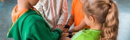 Foto de Vista cruzada de los niños juntos en círculo con las manos unidas, tiro panorámico. - Imagen libre de derechos