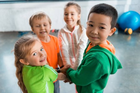 Photo pour Selective focus of multicultural children standing together in circle with united hands in gym - image libre de droit