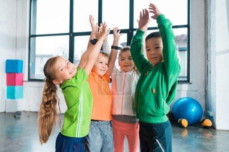 Foto de Niños multiétnicos levantando las manos juntos en el gimnasio - Imagen libre de derechos