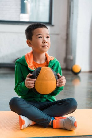 Selective focus of asian boy holding ball and sitting with crossed legs on fitness mat in sports center