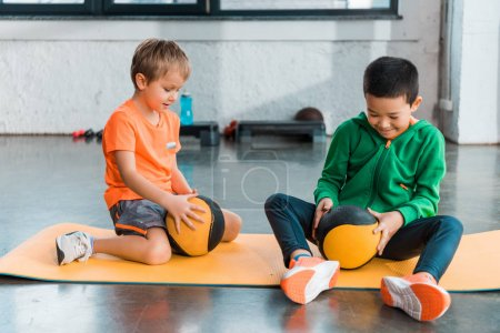 Photo for Selective focus of multicultural kids looking at balls in hands and sitting on fitness mats in gym - Royalty Free Image