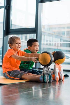 Photo pour Enfants multiculturels mettre des boules sur le bout des orteils et assis sur tapis de fitness dans la salle de gym - image libre de droit