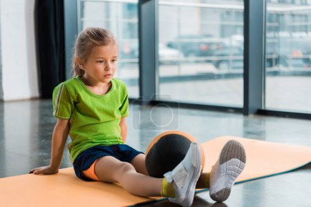 Photo for Child with ball on legs sitting on fitness mat in gym - Royalty Free Image