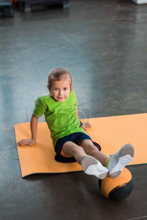 Photo for Child with legs on ball sitting on fitness mat in gym - Royalty Free Image