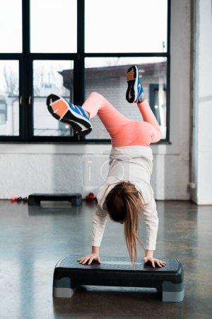 Concentration sélective de l'enfant faisant handstand sur la plate-forme étape dans la salle de gym