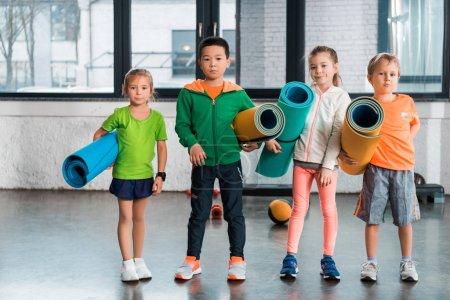 Frontansicht multikultureller Kinder, die Fitnessmatten in der Hand halten und in die Kamera in der Turnhalle schauen
