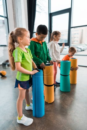 Photo pour Selective focus of multicultural children standing with fitness mats in gym - image libre de droit