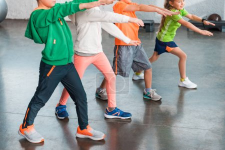 Photo for Cropped view of children with outstretched hands doing lunges in gym - Royalty Free Image