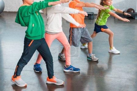 Foto de Vista cruzada de niños con manos extendidas haciendo pulmones en el gimnasio. - Imagen libre de derechos