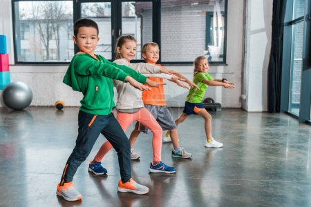 Photo pour Side view of multi-ethnic children with outstretched hands doing lunges in gym - image libre de droit