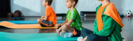 Photo pour Selective focus of children with crossed legs sitting on fitness mats in gym, panoramic shot - image libre de droit