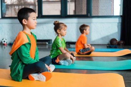 Photo pour Concentration sélective des enfants multiculturels avec les jambes croisées assis sur des tapis de fitness dans le centre sportif - image libre de droit