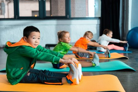 Photo pour Selective focus of multiethnic kids stretching on fitness mats in sports center - image libre de droit