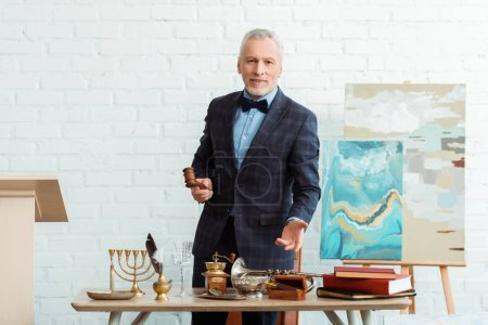 smiling auctioneer holding gavel and pointing with hand at antique objects during auction