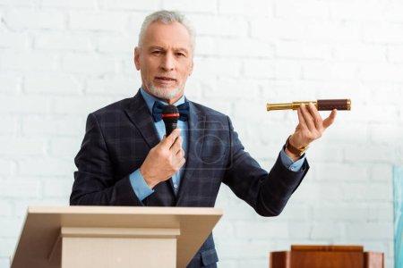 Photo pour Beau commissaire-priseur en costume parlant avec microphone et tenant spyglass pendant la vente aux enchères - image libre de droit