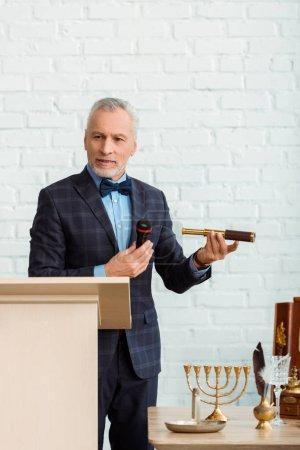 Photo pour Bel encanteur en costume parlant avec un microphone et tenant des vitres volantes pendant l'encan - image libre de droit