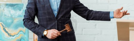Photo pour Plan panoramique de l'encanteur tenant le marteau et pointant à la main pendant la vente aux enchères - image libre de droit