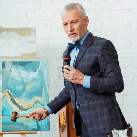 Auktionator im Anzug spricht mit Mikrofon und hält Hammer während Auktion