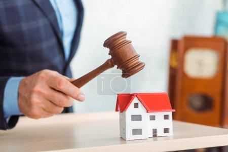 Photo pour Vue recadrée de encanteur frapper modèle de maison avec marteau pendant la vente aux enchères - image libre de droit