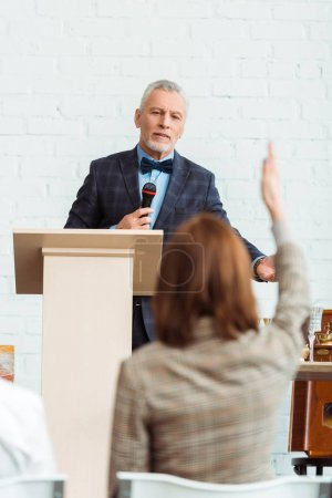 Photo for Selective focus of auctioneer talking with microphone and looking at buyer during auction - Royalty Free Image
