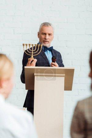 Photo pour Foyer sélectif de l'encanteur parlant avec le microphone et tenant le chandelier pendant la vente aux enchères - image libre de droit