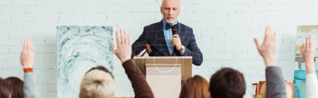 Photo for Panoramic shot of auctioneer holding gavel and microphone and looking at buyers with raised hands during auction - Royalty Free Image