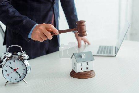Photo pour Crochet vue de l'encanteur frapper modèle de maison avec marteau - image libre de droit