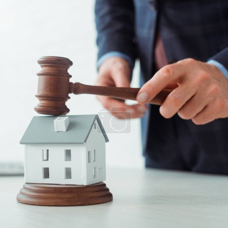 Photo for Cropped view of auctioneer hitting model of house with gavel - Royalty Free Image