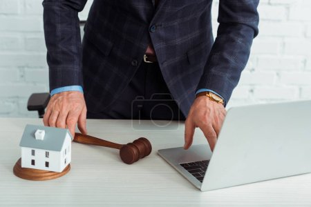 Photo for Cropped view of auctioneer holding gavel and using laptop - Royalty Free Image