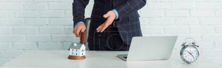 Photo pour Plan panoramique du commissaire-priseur tenant le marteau et pointant à la main vers le modèle de la maison - image libre de droit