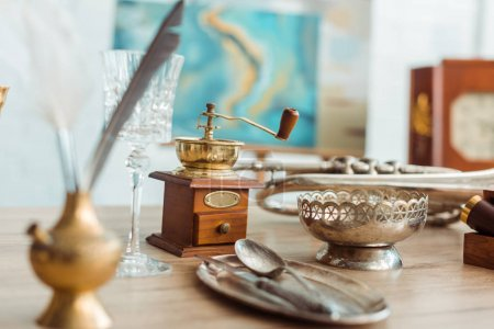 Photo for Selective focus of coffee grinder, glass, ashtray and ancient plate with cutlery - Royalty Free Image