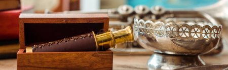 Photo for Panoramic shot of spyglass in box and ancient ashtray on table - Royalty Free Image