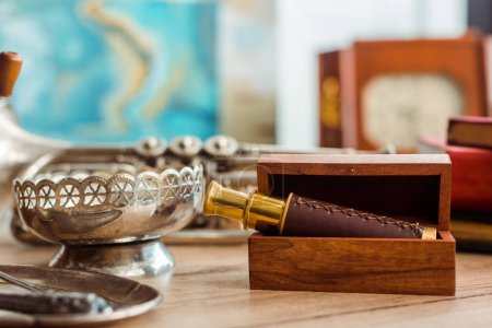 Photo for Selective focus of spyglass in box and ancient ashtray on table - Royalty Free Image