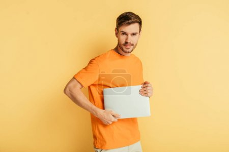 handsome positive man looking at camera while holding closed laptop on yellow background