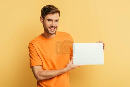Photo pour Jeune homme souriant montrant ordinateur portable fermé et regardant la caméra sur fond jaune - image libre de droit