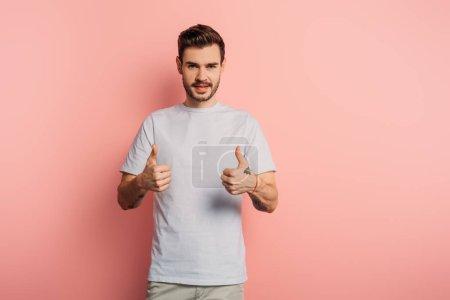 Foto de Sonriente hombre guapo mostrando pulgares hacia arriba mientras mira la cámara sobre fondo rosa. - Imagen libre de derechos
