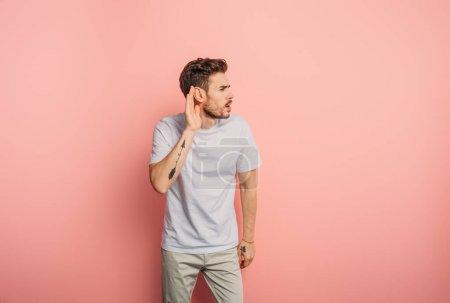 Photo pour Jeune homme confus, en train d'entendre un geste en tenant la main près de l'oreille sur fond rose - image libre de droit