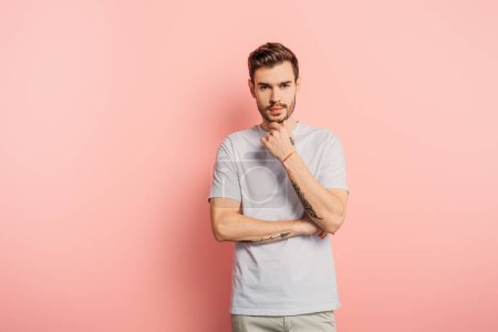 Photo pour Réfléchi jeune homme toucher le menton tout en regardant la caméra sur fond rose - image libre de droit