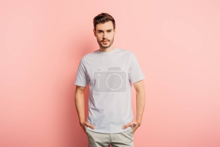 Photo for Handsome, confident young man with hands in pockets looking at camera on pink background - Royalty Free Image