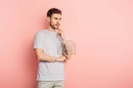 Photo for Handsome pensive man looking away and touching chin on pink background - Royalty Free Image