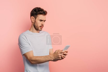 Photo for Shocked young man chatting on smartphone on pink background - Royalty Free Image