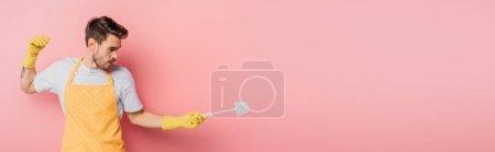 Photo pour Plan panoramique de jeune homme en tablier et gants en caoutchouc imitant l'escrime avec brosse de toilette sur fond rose - image libre de droit