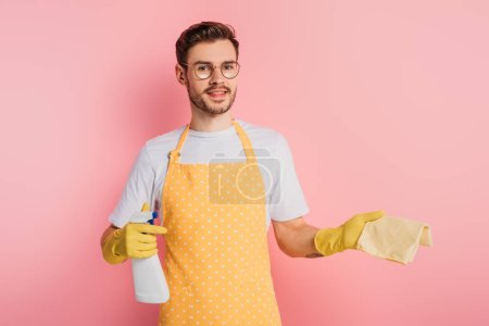 Photo for Cheerful young man in apron and rubber gloves holding spray bottle and rag on pink background - Royalty Free Image