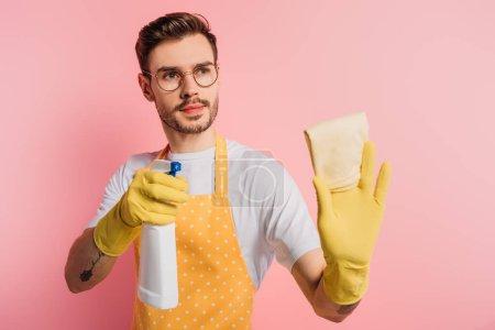 Photo pour Sérieux jeune homme en tablier et gants en caoutchouc tenant vaporisateur et chiffon sur fond rose - image libre de droit