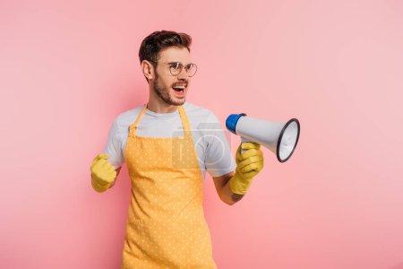 Photo pour Jeune homme irrité en tablier et gants en caoutchouc criant en mégaphone sur fond rose - image libre de droit