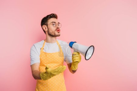 Photo pour Displeased young man in apron and rubber gloves holding megaphone while standing with open arm on pink background - image libre de droit
