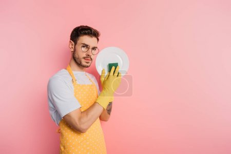 Photo for Serious young man in apron and rubber gloves cleaning plate with sponge on pink background - Royalty Free Image
