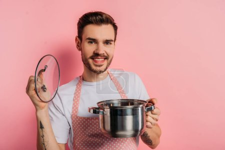 Photo for Cheerful young man in apron opening saucepan on pink background - Royalty Free Image